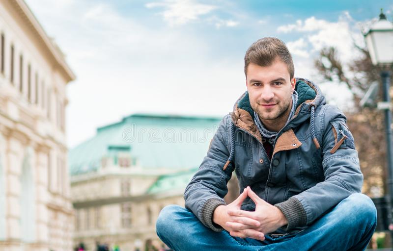 Young handsome man sitting. Gorgeous guy looking at camera royalty free stock photography