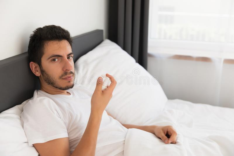 A young handsome man is sitting in his bed. stock images