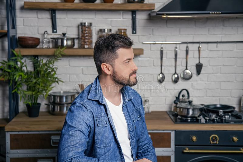 Young handsome man is sitting at the kitchen in the morning looking at the window thinking stock photo