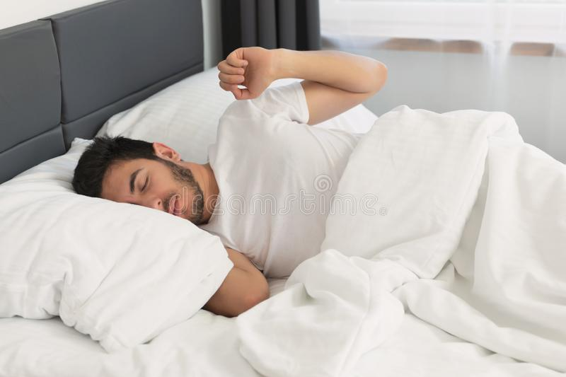 Young handsome man sleeping in his bed. royalty free stock images