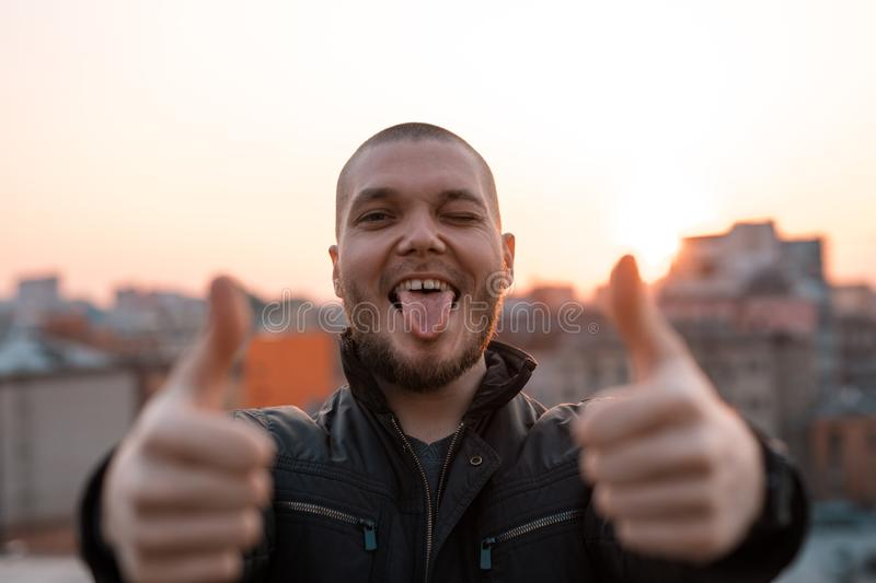 Young handsome man smiles and shows tongue against the backdrop of the city royalty free stock photo