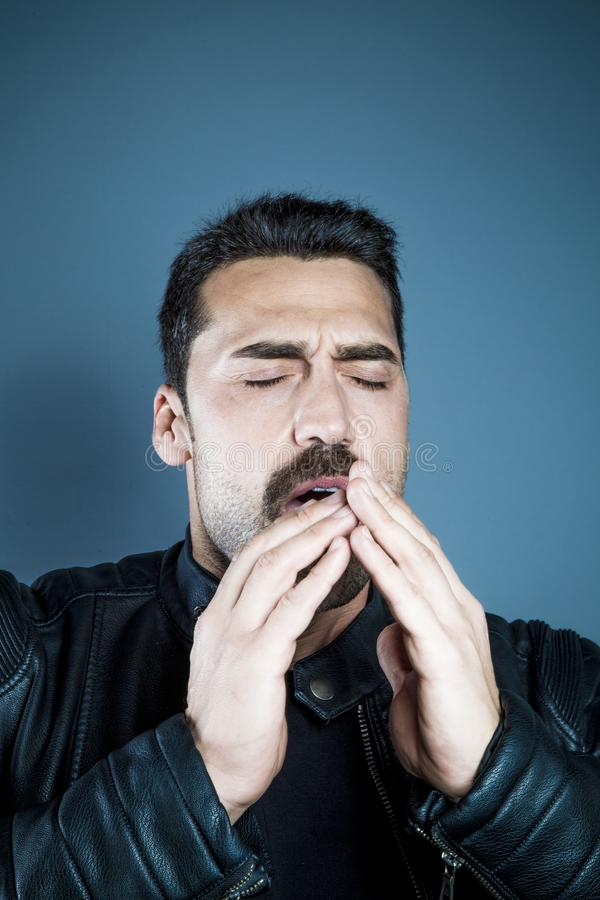 Young handsome man sneezing, close up portrait stock image