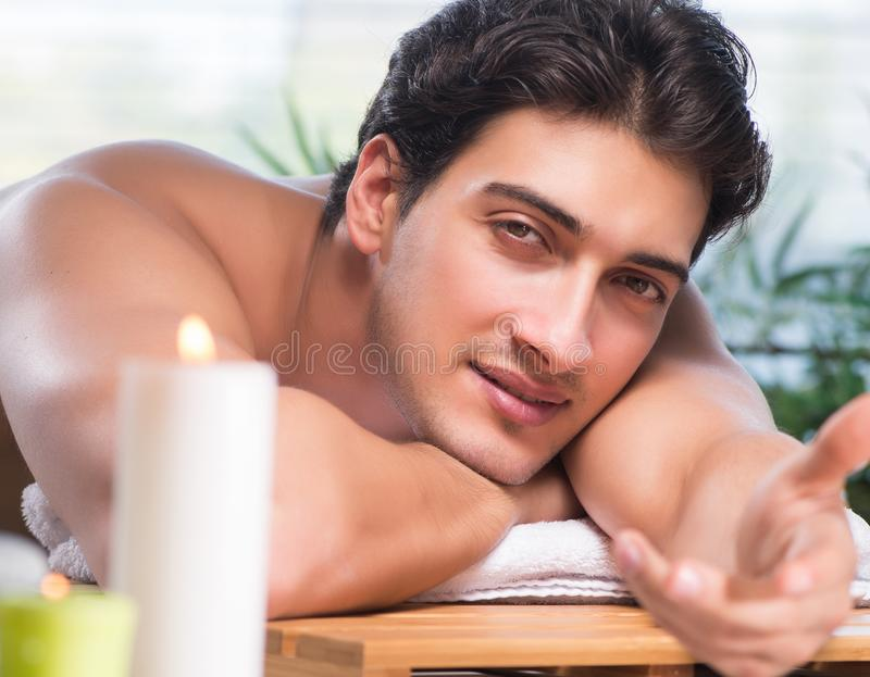 The young handsome man during spa procedure stock photography