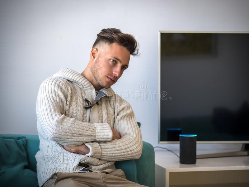 Young man speaking to smart electronic speaker home assistant royalty free stock images