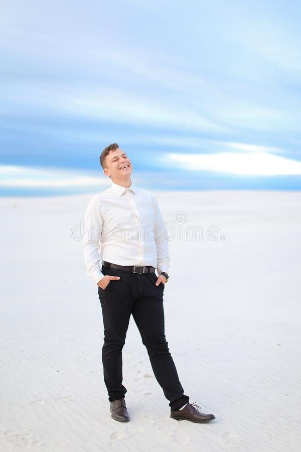Young handsome man standing in winter steppe and wearing white shirt. stock photography