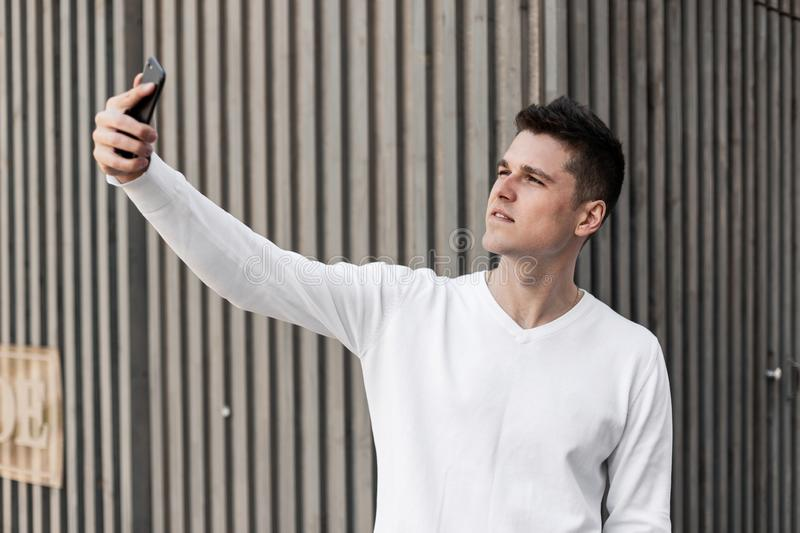 Young handsome man with a stylish hairstyle in a fashionable white shirt makes selfie standing near a gray wooden building stock photos