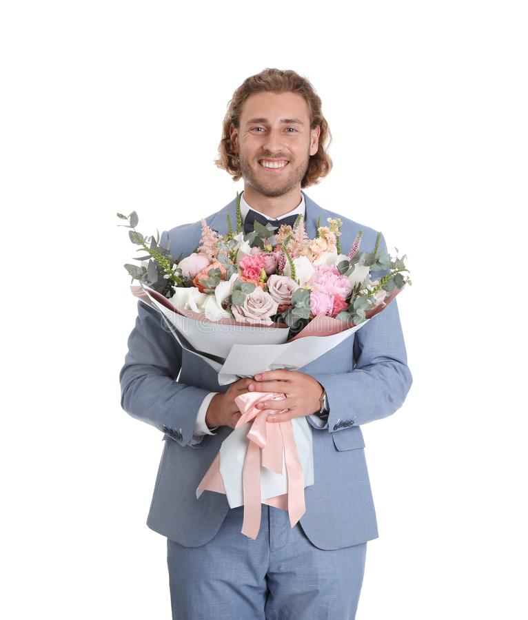 Young handsome man in stylish suit with beautiful flower bouquet royalty free stock image