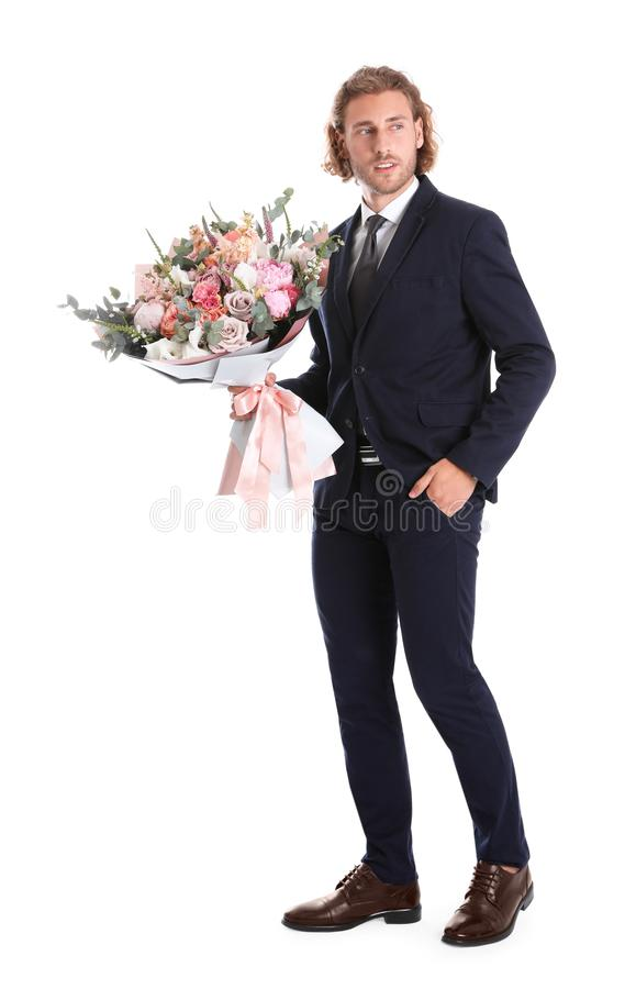 Young handsome man in stylish suit with beautiful flower bouquet on white royalty free stock photos