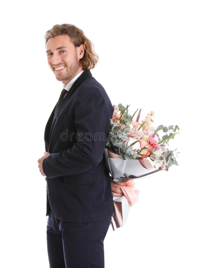 Young handsome man in stylish suit hiding beautiful flower bouquet behind his back stock image