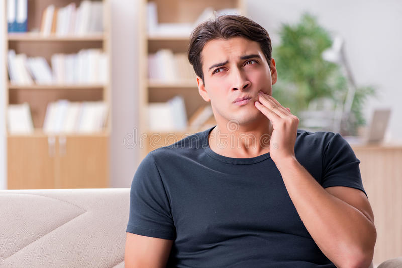The young handsome man suffering from pain stock photo