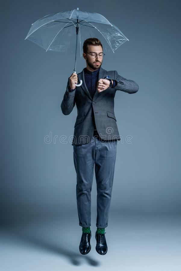 Young handsome man in suit and glasses holding an umbrella and looking. At his watch stock images