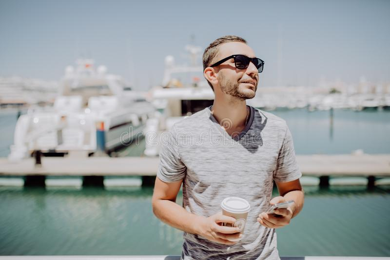 Young handsome man in sunglasses drink coffee to go and talk mobile phone on summer street with yacht harbor on background. Travel. Young handsome man in royalty free stock photography