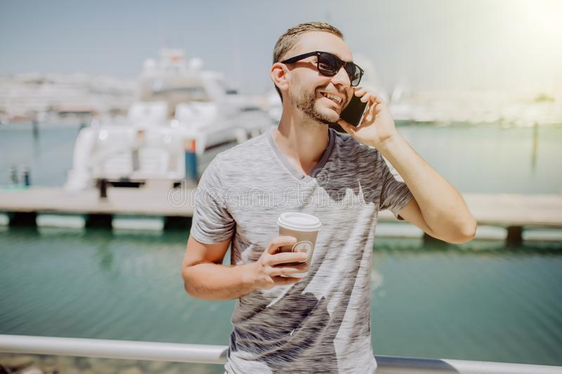 Young handsome man in sunglasses drink coffee to go and talk mobile phone on summer street with yacht harbor on background. Travel. Young handsome man in stock photos