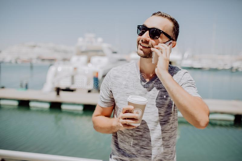 Young handsome man in sunglasses drink coffee to go and talk mobile phone on summer street with yacht harbor on background. Travel. Young handsome man in royalty free stock images