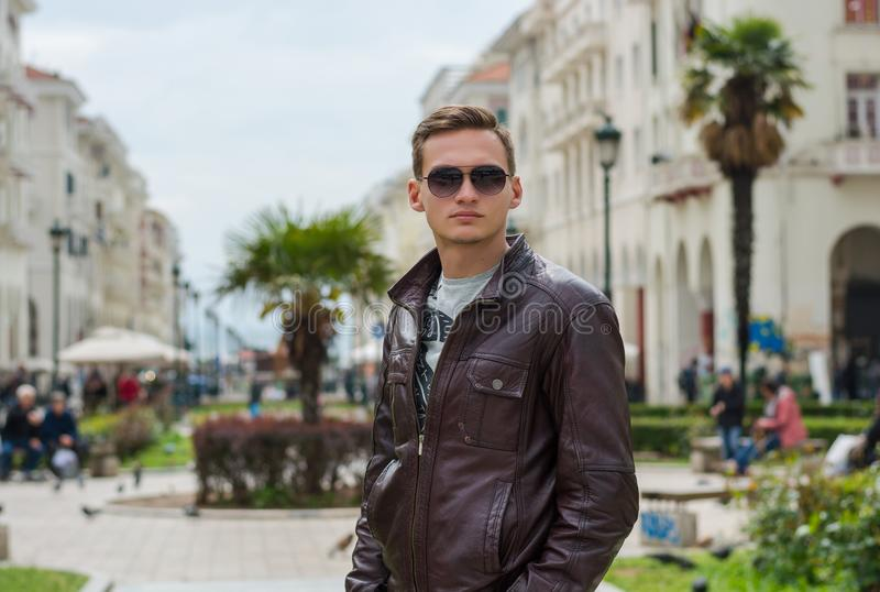 Young handsome man in sunglasses, tourist, on the pedestrian Aristotle Street in the center of the Thessaloniki, Greece stock photo