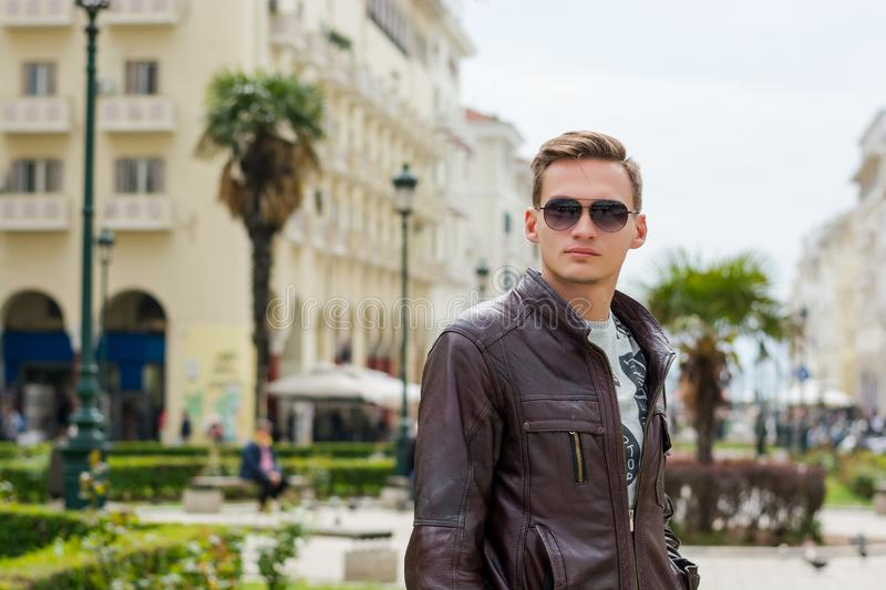 Young handsome man in sunglasses, tourist, on the pedestrian Aristotle Street in the center of the Thessaloniki, Greece stock images