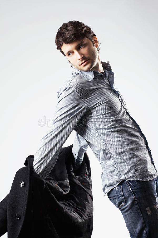 Young handsome man take off a coat stock photos
