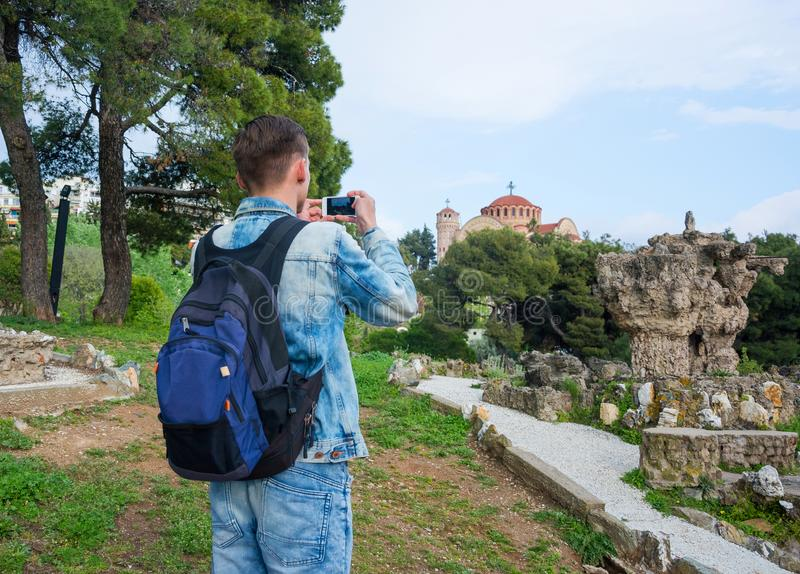Young handsome man taking pictures on a smartphone of the ruins in Pasha`s Gardens and of the Church St. Paul in the in the Ano stock photography