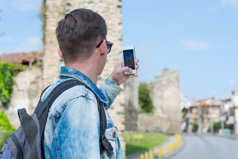 Young handsome man taking pictures on a smartphone the Trigonion Tower Upper Town Fortress in the Thessaloniki, Greece royalty free stock image