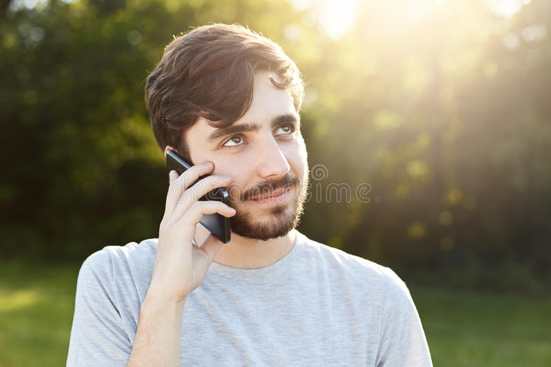 Young handsome man with thick beard and dark big eyes holding smart phone phoning his friend while standing at green background. H royalty free stock photography