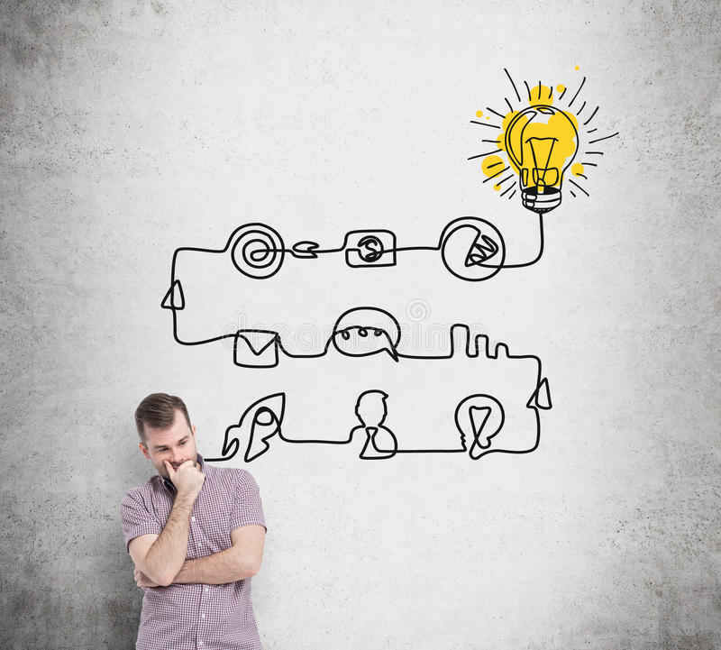 A young handsome man is thinking about the process of developing a new idea. A flowchart is drawn on the concrete wall with differ royalty free stock photography