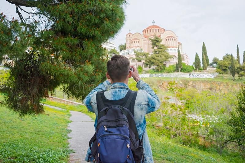 Young handsome man with backpack taking pictures on a smartphone of the Church St. Paul in the in the Ano Poli in Thessaloniki, stock photography