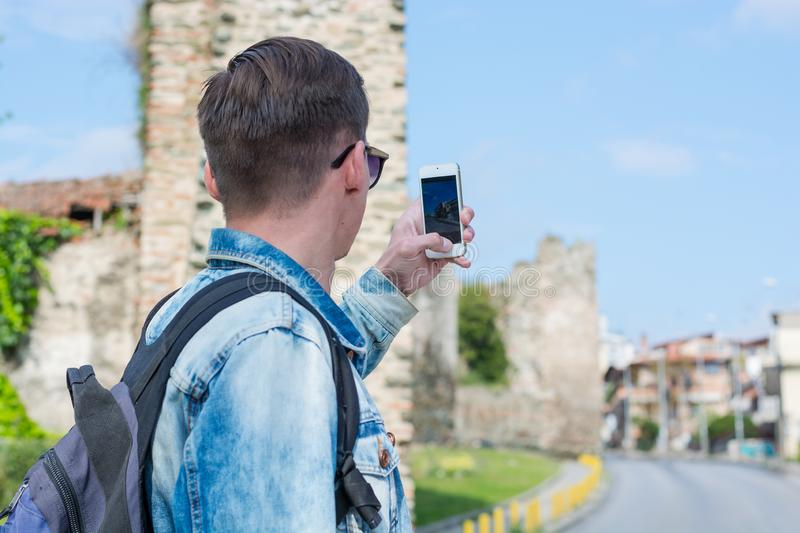 Young handsome man, tourist, with backpack taking pictures on a smartphone the Trigonion Tower in the Thessaloniki, Greece royalty free stock photos