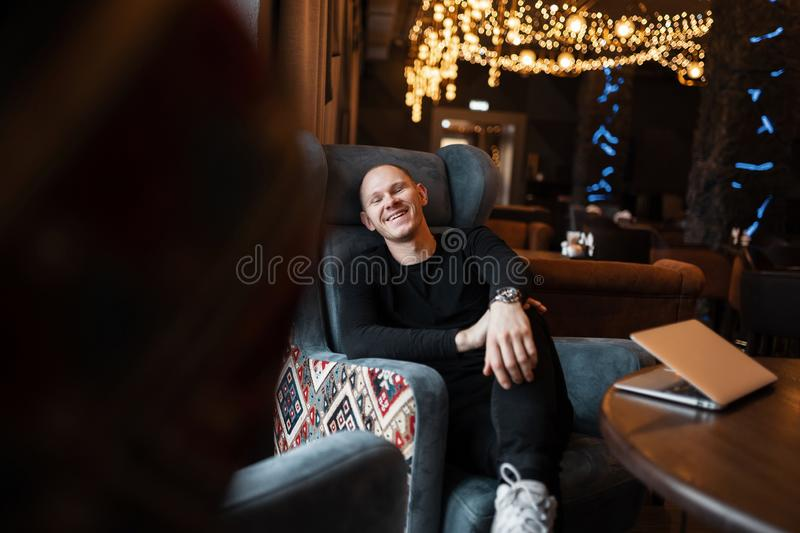 Young handsome man in trendy black clothes sits and laughs at a table on a soft vintage chair in a beautiful expensive restaurant royalty free stock photography