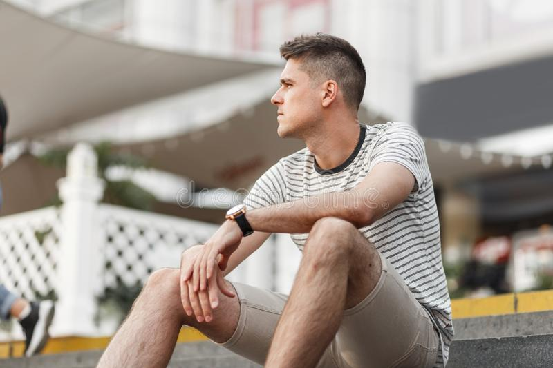 Young handsome man with trendy hairstyle in a stylish striped t-shirt in fashionable beige shorts sits on the stairs in the city royalty free stock images