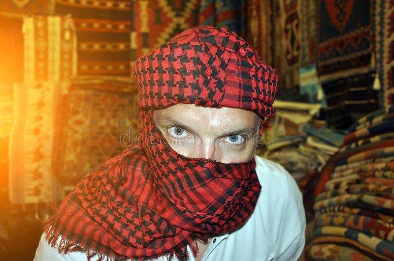 A young handsome man in a turban stares intently at you. Flare stock photo