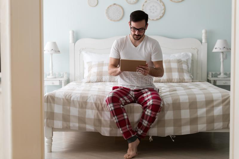 Young handsome man using digital tablet on bed royalty free stock photography
