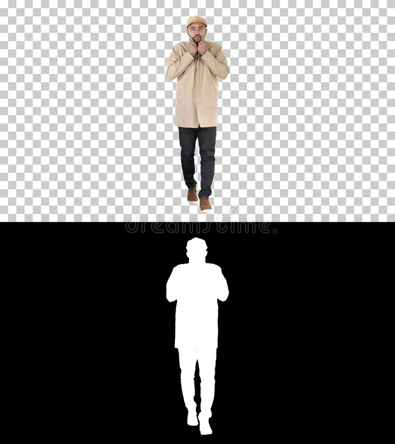 Young handsome man walks and buttons up cloak, Alpha Channel stock photos