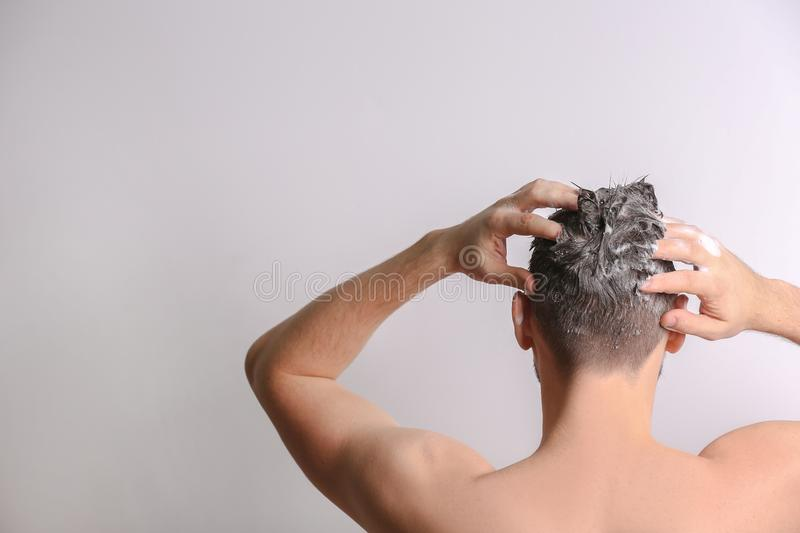 Young handsome man washing hair stock photo