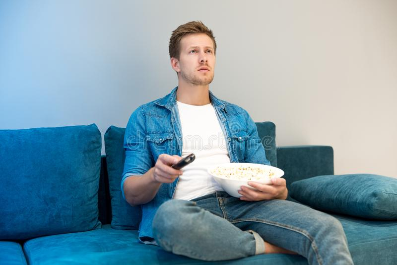 Young handsome man watching movie on the sofa eating popcorn feeling comfortable on the sofa at home looking involved royalty free stock photography