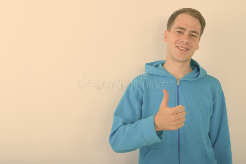 Young handsome man wearing blue hoodie against white background royalty free stock photos