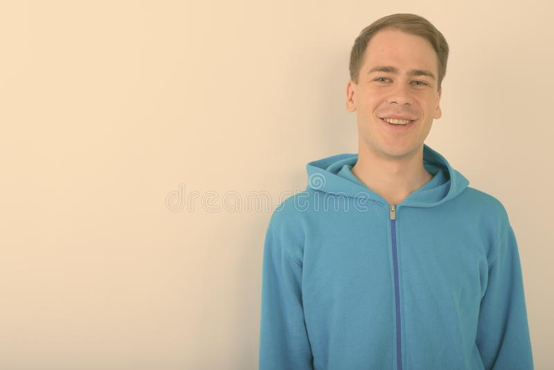 Young handsome man wearing blue hoodie against white background royalty free stock image