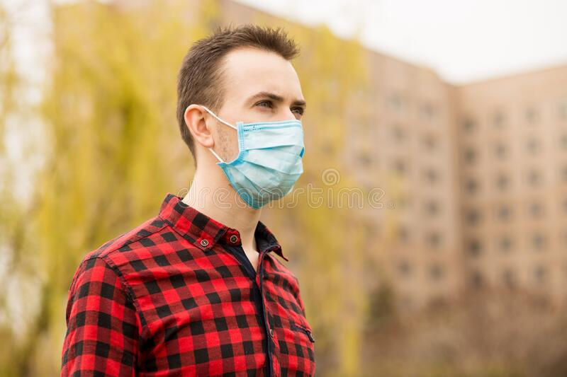 Young handsome man wearing face pollution mask to protect from coronavirus walking alone outdoor by city street. Young handsome man wearing face pollution mask royalty free stock photography