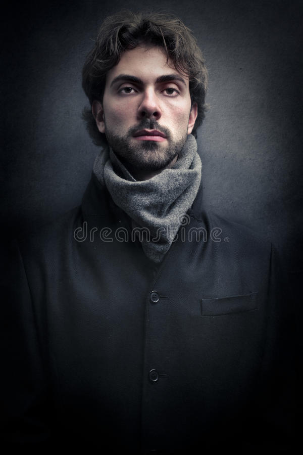 Young handsome man. Wearing a scarf and a coat royalty free stock photos