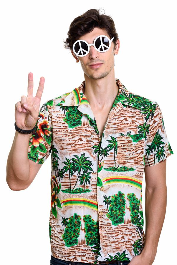 Young handsome man wearing sunglasses with peace sign while givi stock image