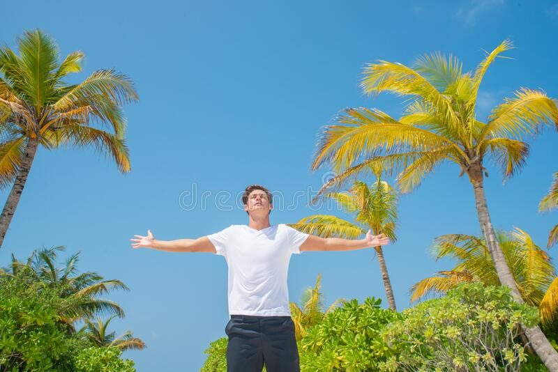 Young handsome man wearing white t-shirt and rising hands on tropical beach at the island luxury resort stock photo