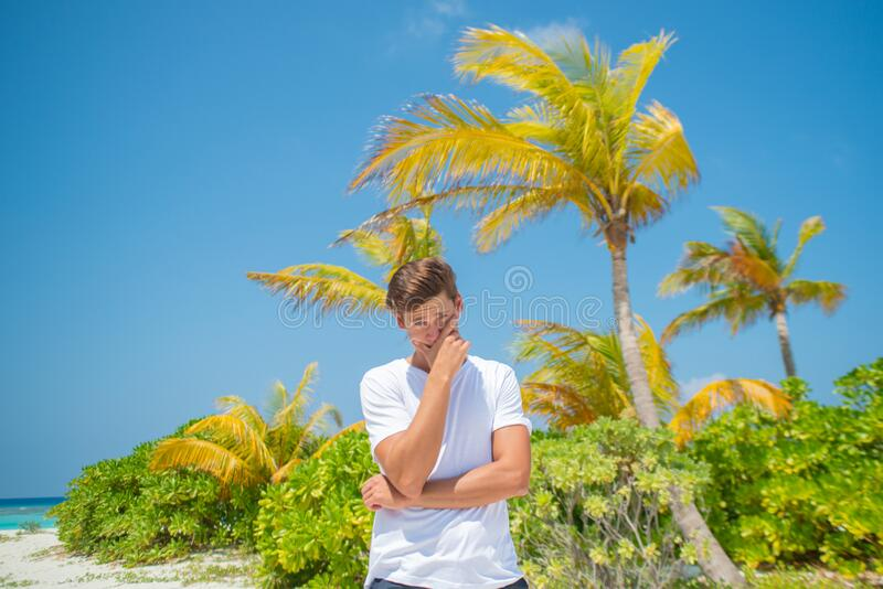 Young handsome man wearing white t-shirt on tropical beach at the island luxury resort royalty free stock photo