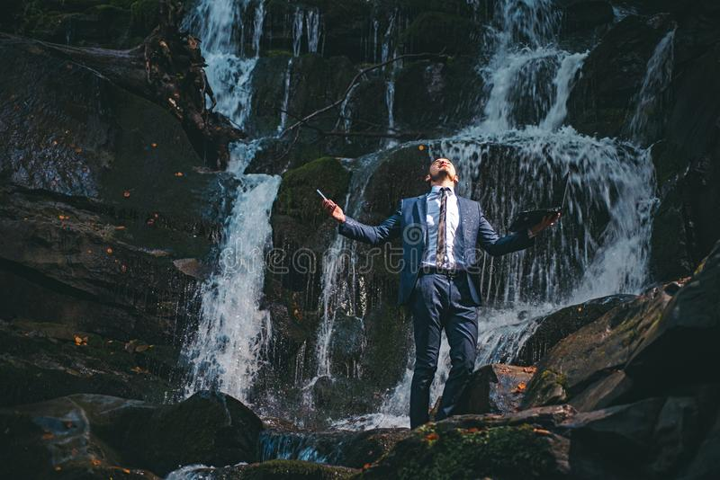 Young handsome man in wet office suit holding Laptop under the water on nature background. Fantasy about the rest. Burnout in the workplace concept royalty free stock photography
