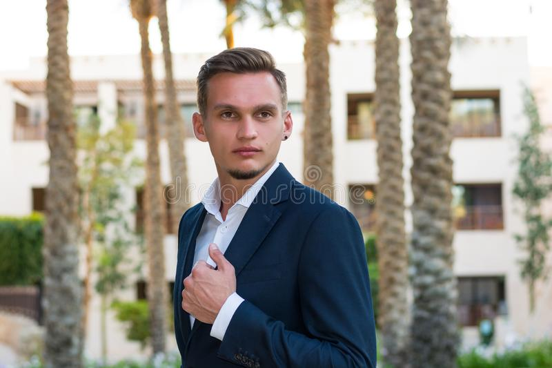 Young handsome man in a white shirt, white trousers and suit stands near the palm tree. Fashion Model stock photo