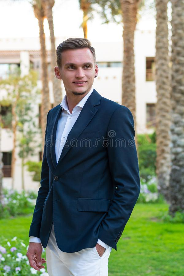 Young handsome man in a white shirt, white trousers and suit stands near the palm tree. Fashion Model royalty free stock images