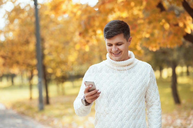 Young handsome man during the work break walking in the autumn park and using smartphone. stock photography