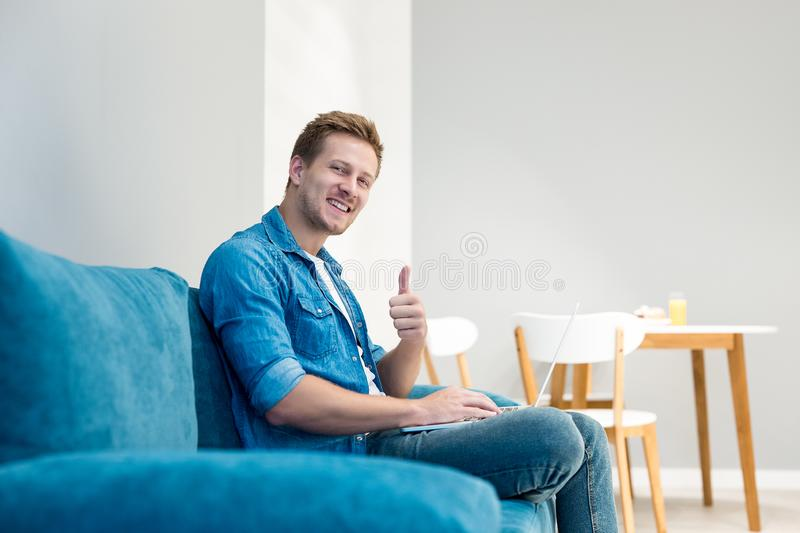 Young handsome man working in his laptop sitting on the comfortable sofa in the livingroom looking happy showing like stock images