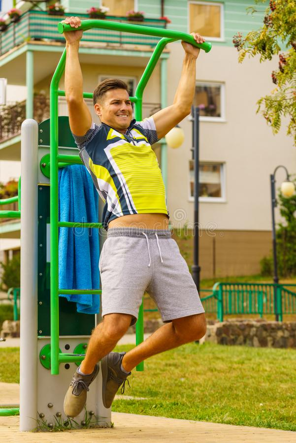 Man doing pull ups in outdoor gym. Young handsome man working out in outdoor gym. Sporty guy flexing his muscles doing pull ups on machine. Staying fit and stock image