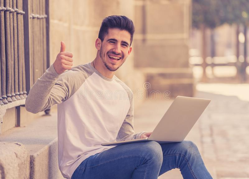 Young handsome man working and studying on laptop in a european stock image