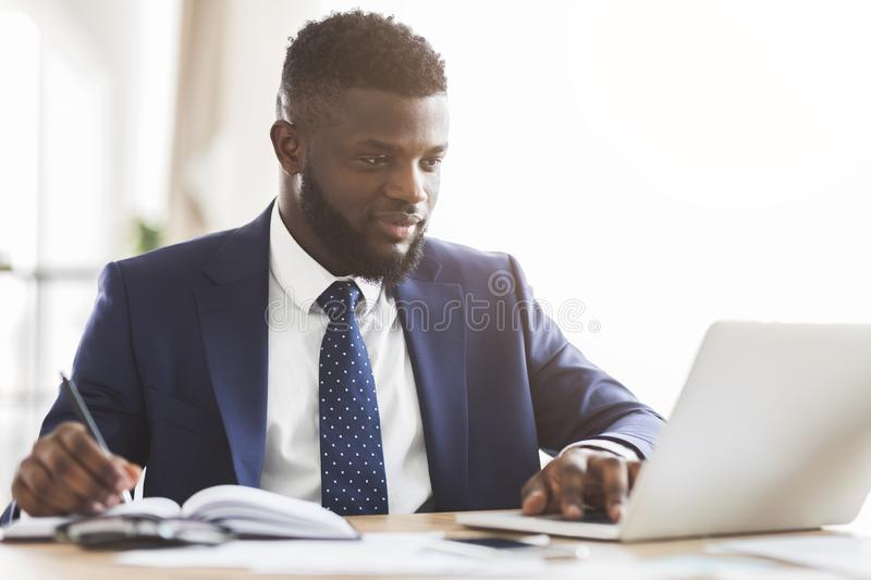 Young handsome manager making market research online stock image