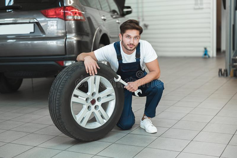 Young handsome mechanic wearing uniform working in car service department fixing flat tire looks pleased. Young handsome mechanic in uniform working in car stock images